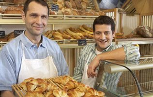 two men posing in their bakery